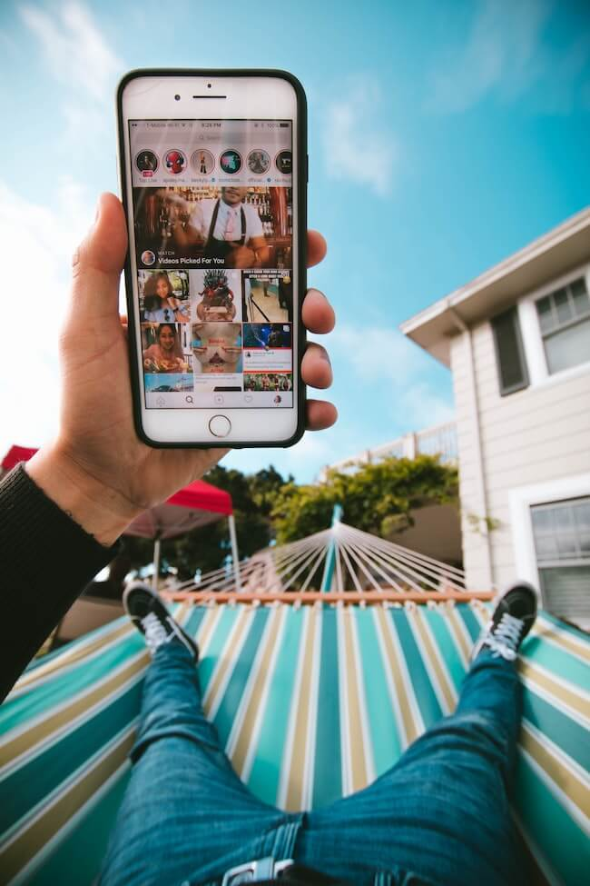 man laying in hammock looking at instagram